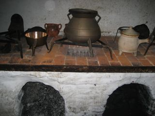 "This is a ""five-burner stovetop,"" a brick cooking surface with five small charcoal-fired fireplaces underneath. The three-legged copper pot on the left would be right at home in a modern kitchen."